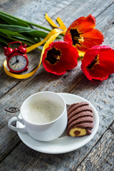 Three colorful tulips on a wooden table. Cup of coffee, cookies. Atmospheric mood. Breakfast