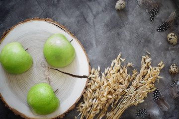 Three halves of green apples on a wooden chair on a table, near a spike of barley and quail eggs