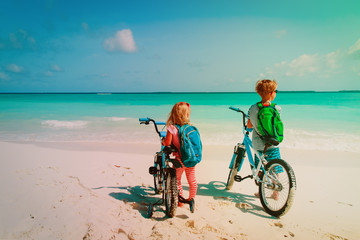happy little boy and girl ride bike on beach