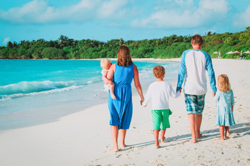 happy family with kids walk on tropical beach