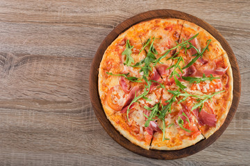 Fresh pizza with prosciutto meat, tomato and green arugula