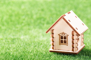 Model of wooden house on green grass background