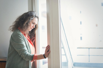 Attractive mature woman with long curly hair standing indoors looking out of a window with a thoughtful expression at something below