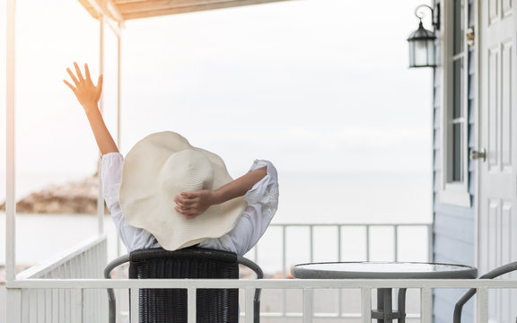 Summer vacation lifestyle with young girl wearing sunscreen hat on sunny day relaxing taking it easy happily sitting on the porch at beach-house on beach front celebrating healthy living life quality