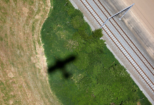 An aerial view of the shadow of a Maule MX-7 aircraft next to railroad tracks near Kortrijk