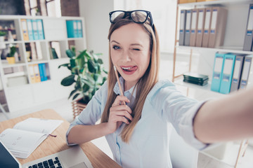 Self portrait of cheerful, attractive, joyful, foolish, stylish, comic, funny woman with glasses on head and hairstyle shooting selfie on front camera, gesture tongue out and blinking with eye