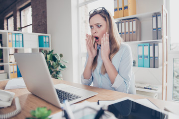 Portrait of attractive, excited, shocked, stressed woman with wide open mouth holding palms near face, looking at screen of computer, sitting in work place, station at desktop