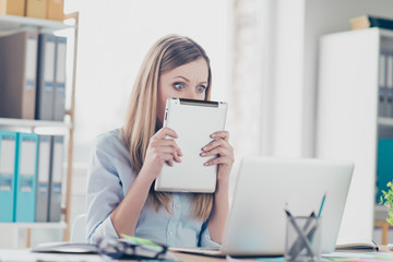 Wondered amazed frustrated secretary cover half face with tablet looking out gadget with wide open eyes looking at laptop having crisis failure bad news sitting at desk in workplace, workstation