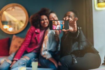 Group of three beautiful young multiracial women sitting in a coffee shop taking a selfie on the mobile phone