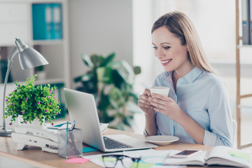 Portrait of charming, attractive, stylish, pretty, cheerful woman having cup of coffee in hands looking at screen of computer, watching film during break time sitting in workplace, workstation