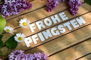 Frohe Pfingsten Wörter auf einem Holtbrett mit Flieder Blumenst