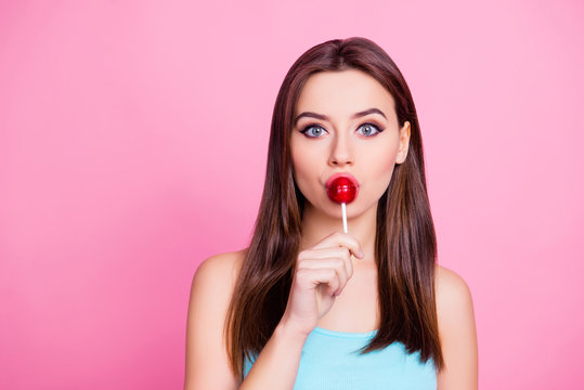 Close up portrait of beautiful cheerful deligthful lovely cute charming wonderful girl kissing red lollipop on stick isolated on pink background, copy space