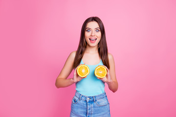Portrait of charming pretty playful fancy funky comic humorous excited cheerful wearing casual blue jeans denim outfit with open mouth girl showing oranges on breast, isolated on pink background