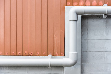 Water pipes on cement wall of building.