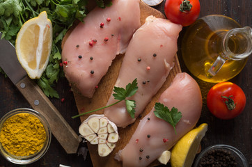 Raw chicken meat on wooden board on table