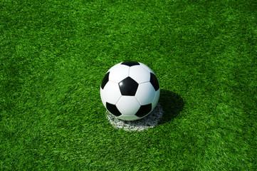 Fussball auf Elfmeterpunkt, grüner Kunstrasen in der Sonne im Sommer