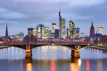 Picturesque view of Frankfurt am Main skyline and Ignatz Bubis Brucke bridge during evening blue hour with mirror reflections in the river, Germany
