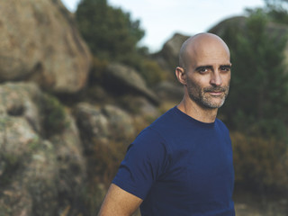 Portrait of mid aged bald man in the forest at sunset wearing a blue t-shirt