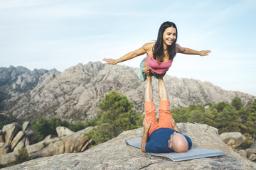 Fit young couple doing acro yoga in rocky scenery at the forest. Man lying on rocks and balancing woman in his feet