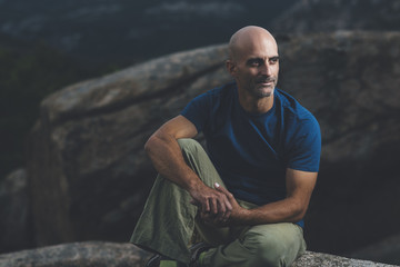Portrait of mid aged bald man seated in a rock in the forest at sunset wearing a blue t-shirt