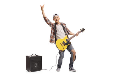 Teenager with an electric guitar and an amplifier making a rock gesture