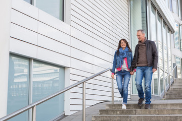 Happy casual middle-aged couple walking through town descending an exterior flight of stairs chatting and smiling with copy space