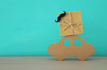 Image of wooden car with gift box on the roof, present for dad. Father's day concept.