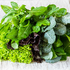 Leaves of green and red lettuce, rucola, kale, amaranth, spinach on white table