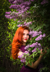 Beautiful red-haired woman with a lilac branch. Portrait of beautiful woman with red hair in spring garden
