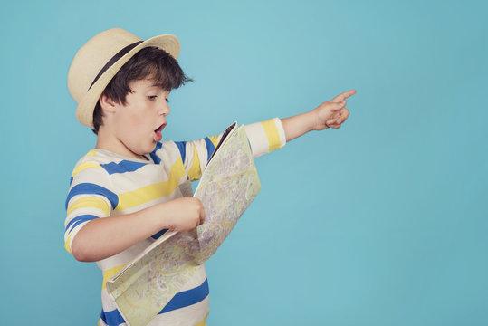 niño con sombrero y mapa sobre fondo azul