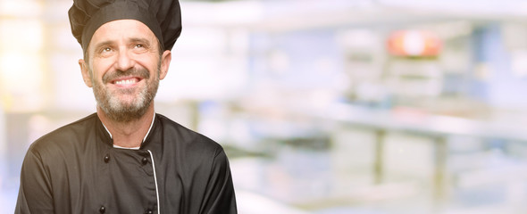 Senior cook man, wearing chef hat thinking and looking up expressing doubt and wonder at restaurant kitchen