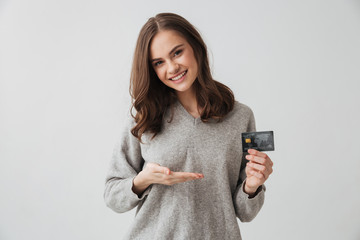Pleased brunette woman in sweater holding credit card