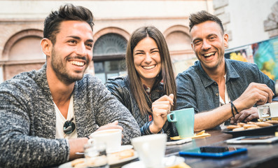 Happy friends talking and having fun at pub restaurant drinking cappuccino and hot tea - Young people together at fashion cafeteria - Friendship concept with men and women at coffee bar - Cold filter