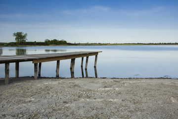 Wooden bridge to the lake and dry shore.