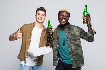 Portrait of a two international happy young men drinking beer and eating snacks while standing isolated over yellow background
