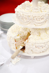 A beautiful white two-layer wedding cake with a cut piece.