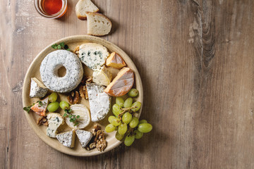 Cheese plate assortment of french cheese served with honey, walnuts, bread and grapes on ceramic plate over wood texture background. Top view, copy space.