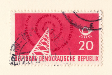 An old red est german stamp with an image of a radio transmitter