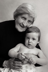 old gray-haired grandmother sits with a small grandson