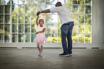 Father helping his daughter practice her ballet.