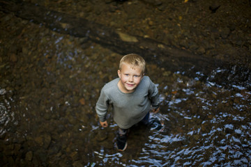 Portrait of young boy looking up while standing  in the shallows of a river.