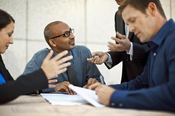 Business people discuss blueprints.