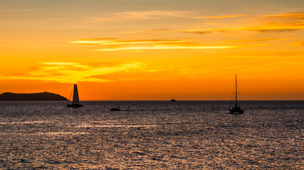 sunset on ibiza island with sailboats in the background
