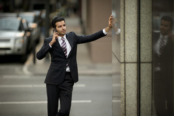 Mid adult businessman talking on a cell phone while standing outside a building.