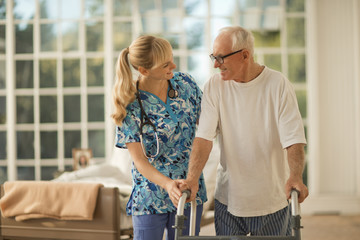 Young nurse holding hands with a senior man.