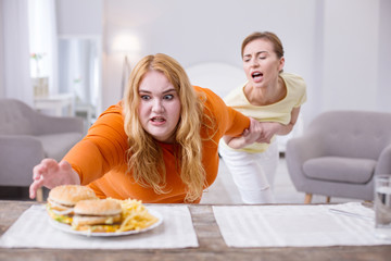 Stop. Excited stout woman reaching for a sandwich and her friend holding her
