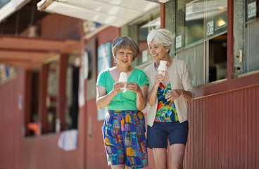 Two smiling senior women getting ice cream together while on vacation.