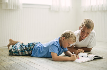 Teenage boy lying on the floor helping his younger brother with homework.