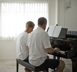 Mature adult man sitting at a piano with his teenage son.