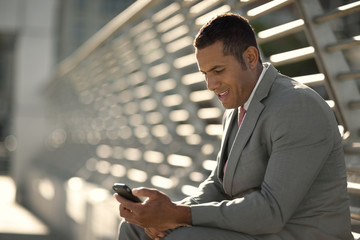 Smiling mid adult business man sending a text message on his phone.